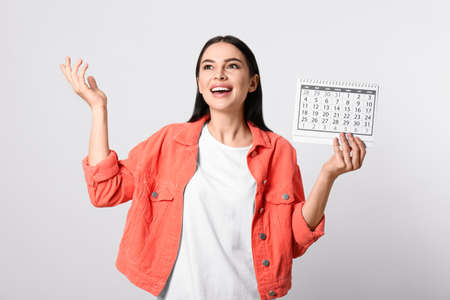 Emotional young woman holding calendar with marked menstrual cycle days on light background