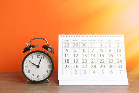 Calendar and alarm clock on wooden table against orange background Imagens