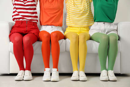 Women wearing bright tights sitting on sofa indoors, closeup Stock Photo
