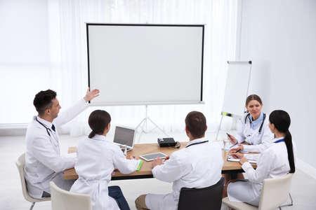 Equipo de médicos con proyector de video durante la conferencia en interiores Foto de archivo