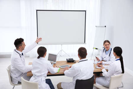 Zespół lekarzy korzystający z projektora wideo podczas konferencji w pomieszczeniu Zdjęcie Seryjne
