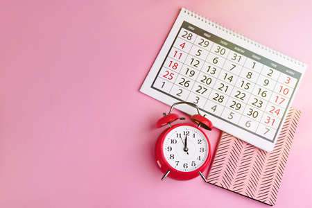 Calendar, notebook and alarm clock on pink background, flat lay. Space for text