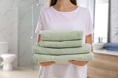 Woman holding fresh towels in bathroom, closeup Фото со стока