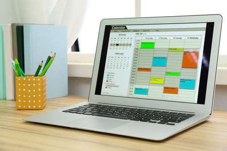 Moderner Laptop mit Kalender auf dem Bildschirm im Büro Standard-Bild