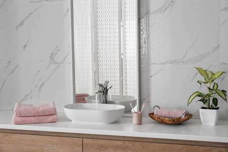 Modern mirror and vessel sink in stylish bathroom Фото со стока