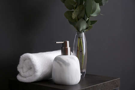 Clean soft towel and soap dispenser on stand near black wall Фото со стока