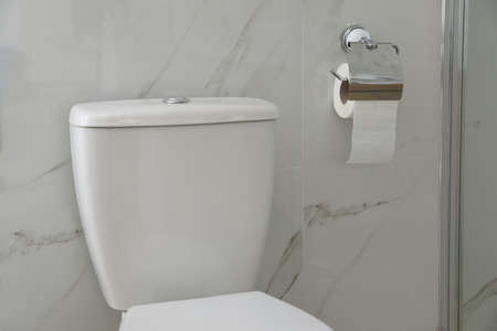 Modern toilet and holder with paper roll indoors Stok Fotoğraf