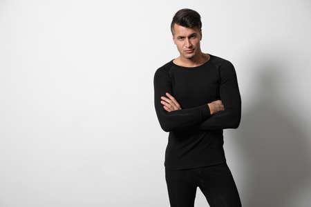 Uomo che indossa biancheria intima termica su sfondo grigio chiaro. Spazio per il testo