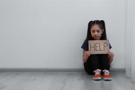 Sad little girl with sign HELP sitting on floor indoors, space for text. Child in danger