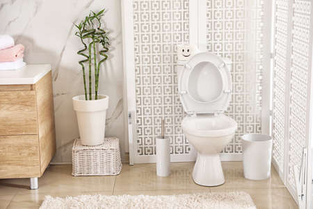Modern toilet bowl with roll of paper in bathroom Standard-Bild
