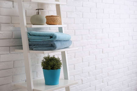 Clean soft towels and soap dispenser on shelves near white brick wall. Space for text