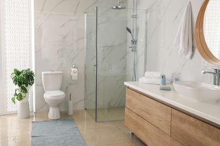Toilet bowl near shower stall in modern bathroom
