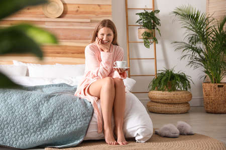 Woman drinking coffee in bedroom with green plants. Home design ideas Foto de archivo - 135498049