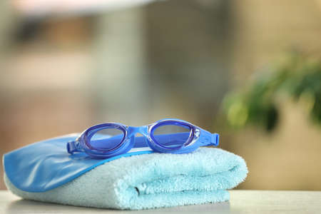 Swimming cap, goggles and towel against blurred background. Space for text