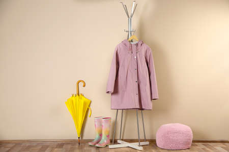 Yellow umbrella, raincoat and rubber boots near beige wall