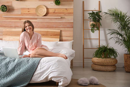 Woman using laptop in bedroom with green plants. Home design ideas Foto de archivo - 135498062
