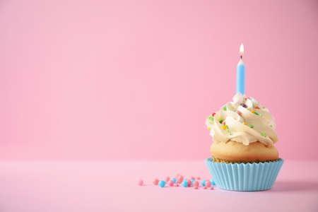 Heerlijke verjaardag cupcake met kaars op roze achtergrond. Ruimte voor tekst