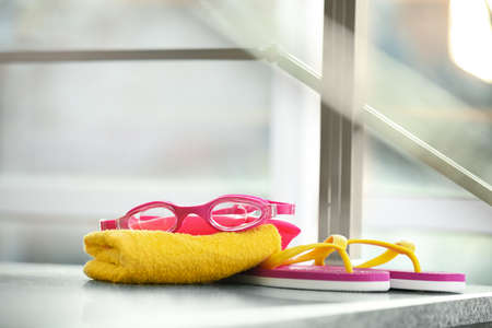 Swimming cap, goggles, flip flops and towel against blurred background. Space for text