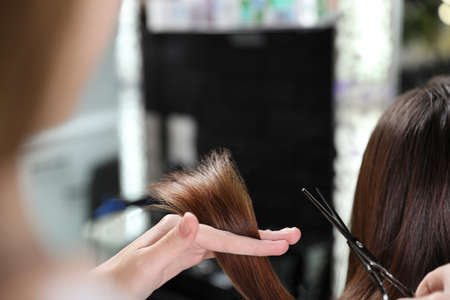 Hairdresser making stylish haircut with professional scissors in salon, closeup