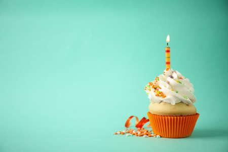 Pyszne ciastko urodzinowe ze świecą na jasnozielonym tle. Miejsce na tekst