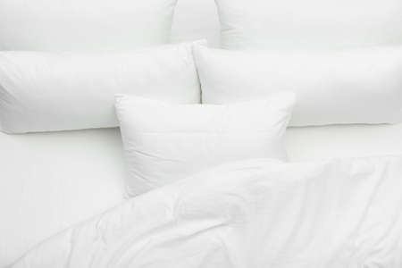 Almohadas blancas suaves y una manta en la cama, vista superior
