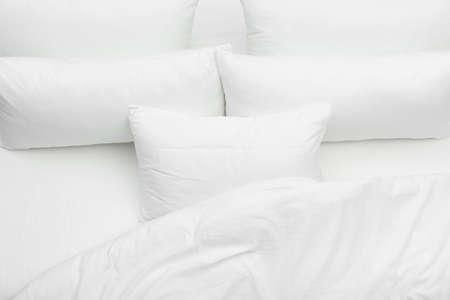 Oreillers blancs doux et couverture sur le lit, vue de dessus