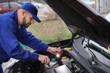 Young mechanic with flashlight fixing car outdoors Stock Photo