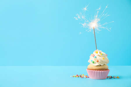Birthday cupcake with sparkler on light blue background. Space for text