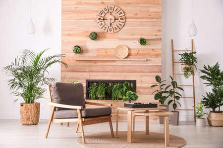 Interno elegante del soggiorno con poltrona, piante verdi e giardino zen in miniatura. Idee di design per la casa