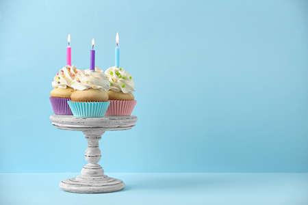 Urodzinowe babeczki ze świecami na jasnoniebieskim tle, miejsce na tekst Zdjęcie Seryjne