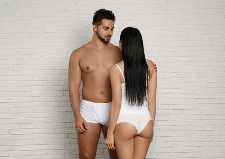 Young couple in white underwear near brick wall