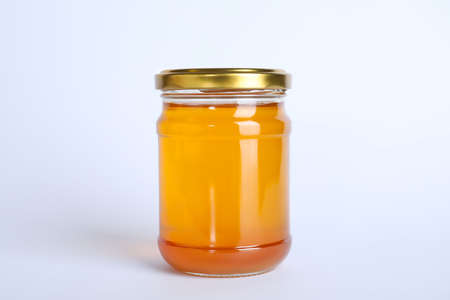 Glass jar of sunflower honey isolated on white