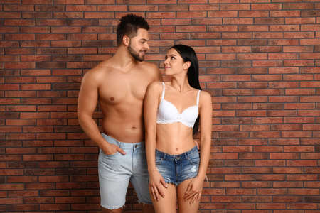 Young woman in underwear and denim shorts with her boyfriend near brick wall Banque d'images - 135498172