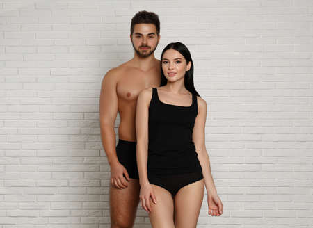 Young couple in black underwear near white brick wall