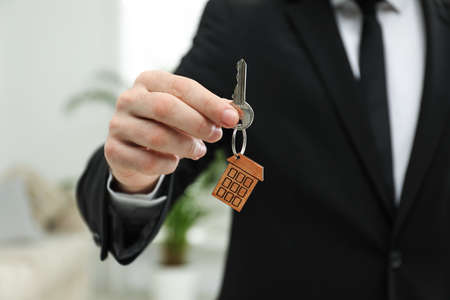 Real estate agent holding house key with trinket indoors, closeup Imagens