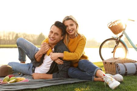 Felice giovane coppia che fa picnic vicino al lago in una giornata di sole Archivio Fotografico