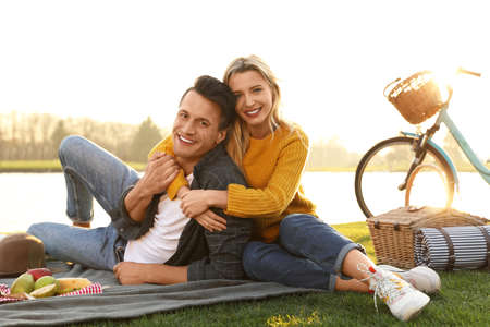 Happy young couple having picnic near lake on sunny day Stock Photo