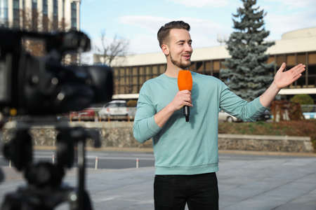 Young male journalist with microphone working on city street
