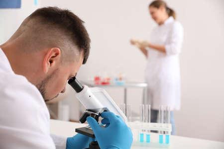 Científico con microscopio en la mesa y colega en laboratorio. Investigación médica