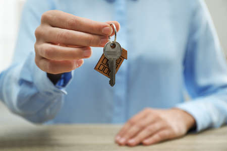 Real estate agent holding house key with trinket at wooden table, closeup