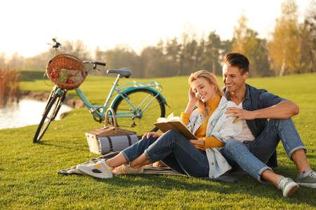 Felice giovane coppia che legge un libro mentre fa un picnic all'aperto
