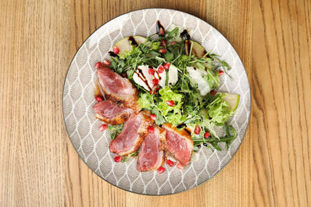 Delicious salad with roasted duck breast served on wooden table, top view