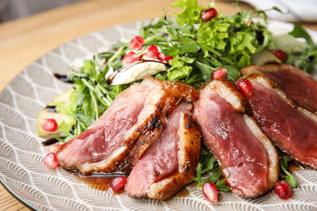 Delicious salad with roasted duck breast on plate, closeup