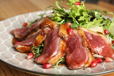 Delicious salad with roasted duck breast served on wooden table, closeup Stok Fotoğraf