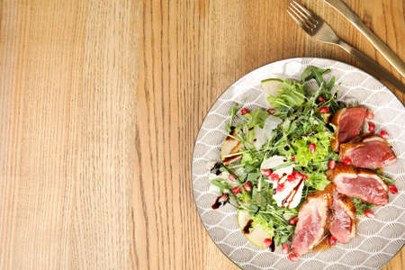 Delicious salad with roasted duck breast served on wooden table, flat lay. Space for text Stok Fotoğraf