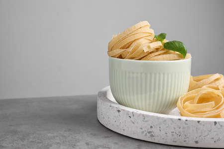 Pâtes tagliatelles non cuites sur table sur fond gris. Espace pour le texte Banque d'images