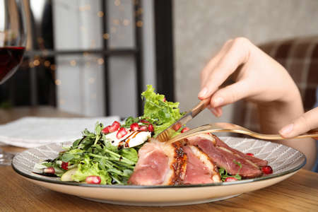Woman eating delicious salad with roasted duck breast at wooden table, closeup Stok Fotoğraf