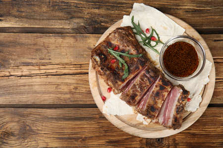 Delicious grilled ribs served on wooden table, top view