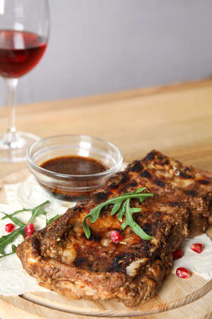 Delicious grilled ribs on wooden board, closeup. Space for text