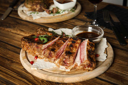 Delicious grilled ribs served on wooden table